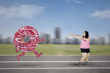 Picture of obese woman chased by tasty donut while running on the track. Shot with blur city background Banco de Imagens