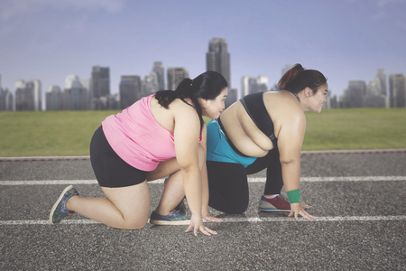 Side view of two obese women ready to run while kneeling on the track with city modern background Stock Photo