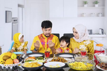 Picture of young family praying together before breaking fast while sitting at the dining table. Shot in the kitchen