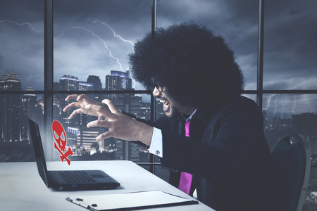 Angry business african american with virus error message Stock Photo
