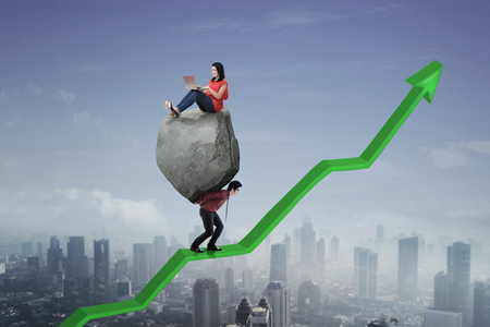 Image of Asian businessman lifting a stone with his leader using a laptop while walking on an upward arrow