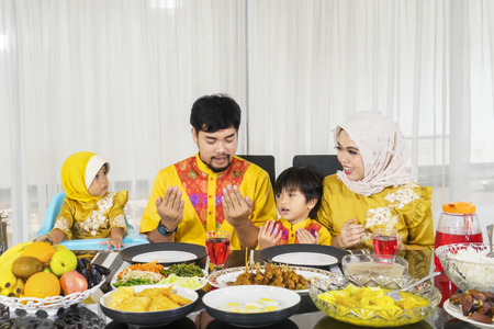 Muslim family sitting at the dining table while praying together before their breaking fast. Shot at home