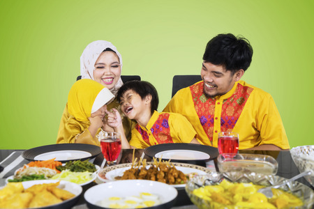 Asian family wearing Islamic clothes while laughing together and sitting in the dining table. Shot with green screen