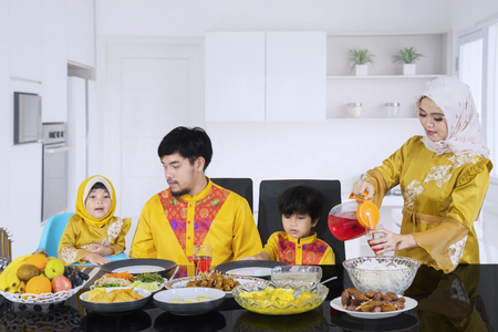 Picture of beautiful woman pouring syrup in a glass for her family before breaking the fast in the kitchen