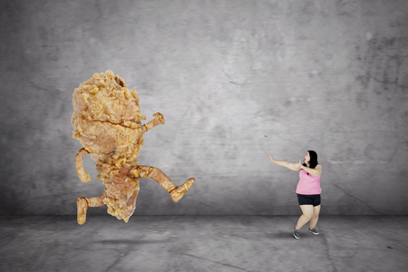 Overweight woman getting a hallucination while escaping from a fried chicken