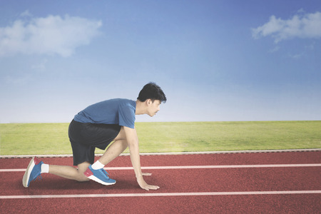 Young man in start position to run while crouched in the track Foto de archivo