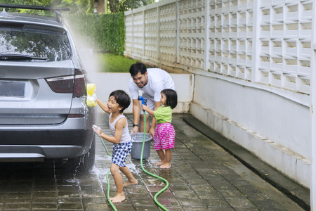 Picture of two little children helping their father while washing a car together