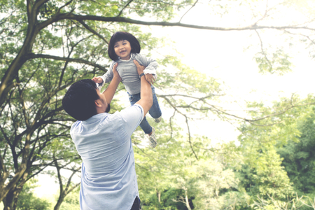 Portrait of cute little girl being lifted by her father while playing together in the park Stock Photo