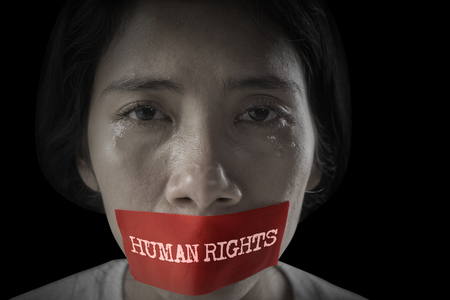 Image of Asian woman crying with her mouth covered by text of human rights on the red tape