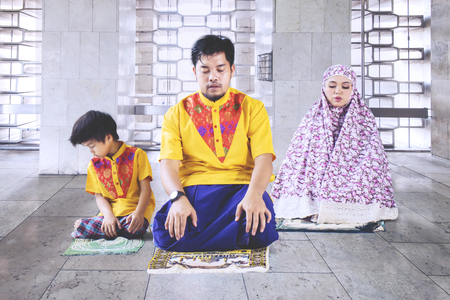 Picture of Asian family sitting on the mat while doing Salat together in the mosque
