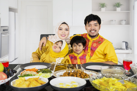 Portrait of Muslim family breaking their fast together while sitting near the dining table. Shot in the kitchen
