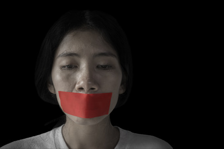 Picture of Asian woman looks desperate with her mouth covered by red tape