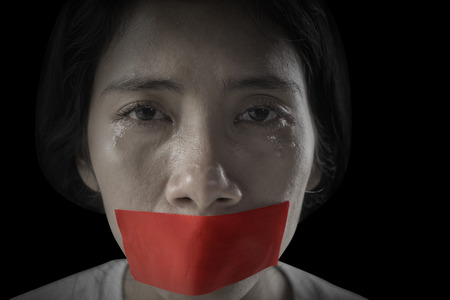 Image of Asian woman looks sad with her mouth covered by red tape Zdjęcie Seryjne