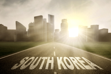 Picture of empty road with word of South Korea and bright sunlight toward a city Stock Photo