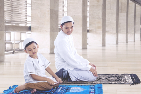 Muslim father and son praying in Istiqlal mosque, Jakarta Indonesia Stock Photo
