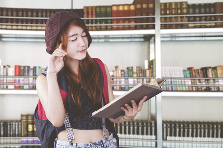 Asian female student learn and reading book in a library