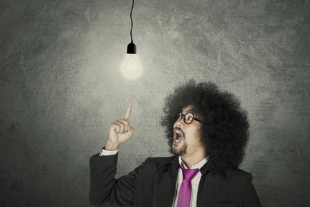 Aha Moment: Businessman with glowing light bulb over grey background