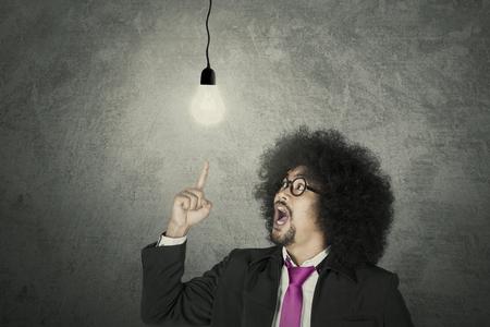 Aha Moment: Geschäftsmann mit leuchtender Glühbirne über grauem Hintergrund