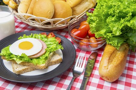 Image of a homemade egg sandwich with assorted breads and milk on the dining table Stock Photo