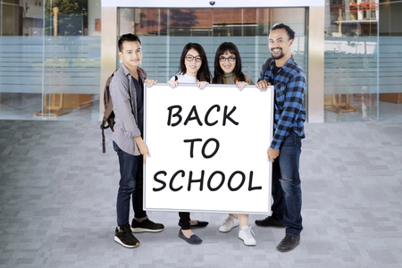 Group of college students holding a white board saying back to school