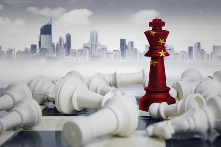 Image d'un roi d'échecs avec le drapeau de la Chine battant des pièces d'échecs blanches. Tourné avec la ville moderne Banque d'images
