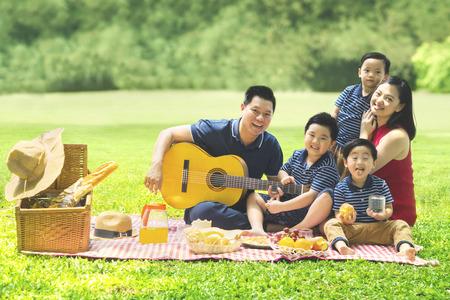 Chinesische Familie, die in die Kamera lächelt, während sie eine Gitarre spielt und zusammen im Park singt