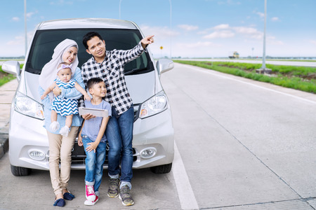 Muslim family using a digital tablet and pointing at something while sitting in front of their car on the highway 写真素材