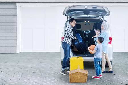 Picture of Muslim family preparing suitcase into a car for holiday while standing together in the garage