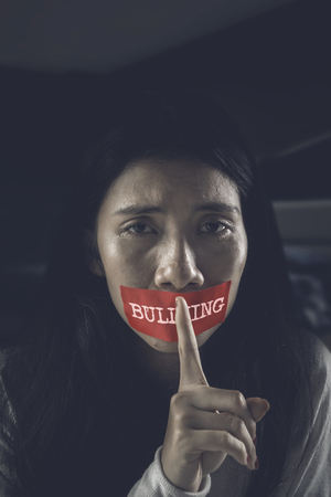 Asian girl making a quiet gesture while sitting in the dark room with her mouth covered by bullying word on a red tape