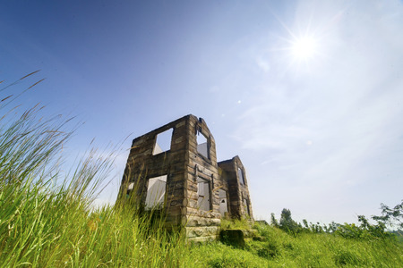 Low angle view of beautiful abandoned house overgrown with bushes under blue sky