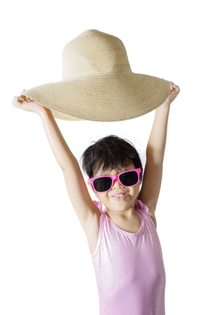 Portrait of little girl looks happy while wearing swimwear and lifting her hat, isolated on white background