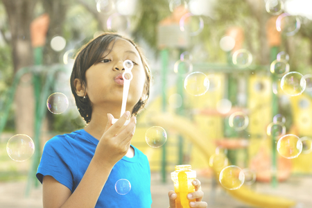 Portrait of cute little girl playing with soap bubbles and standing in the playground