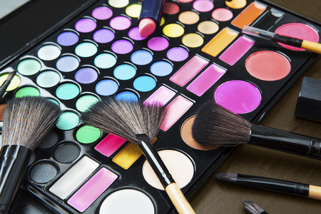 Closeup of professional makeup palette with variety cosmetic brushes and lipstick