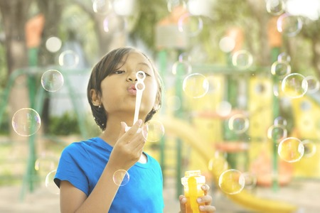 Image of adorable little girl blowing soap bubbles while playing in the playground