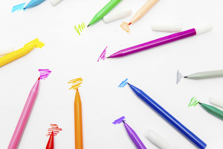 Closeup of colorful marker pens with scribbles, isolated on white background