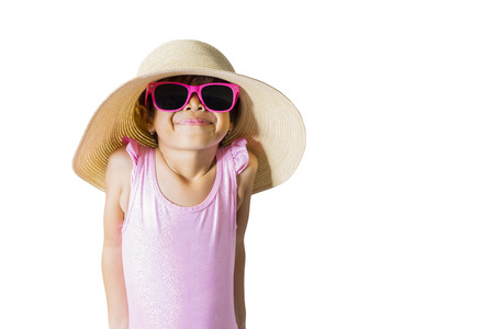 Summer vacation concept. Cute little girl wearing sunglasses and hat while standing with shy expression, isolated on white background Stock Photo