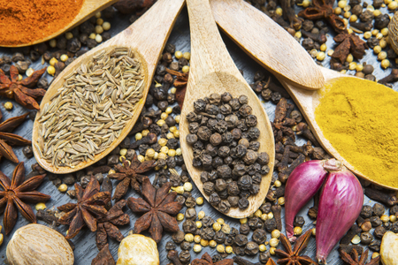 Closeup of assorted spices with wooden spoons and red onions above the table Stock Photo