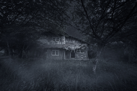 Image of spooky wooden house with damaged rooftop at night time