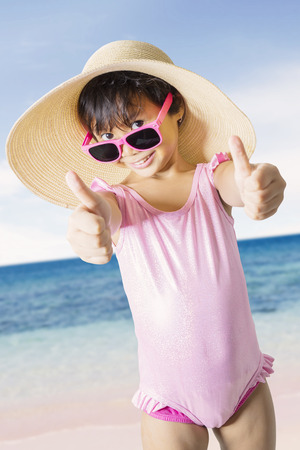 Summer vacation concept. Cute little girl showing thumbs up and standing on the coast