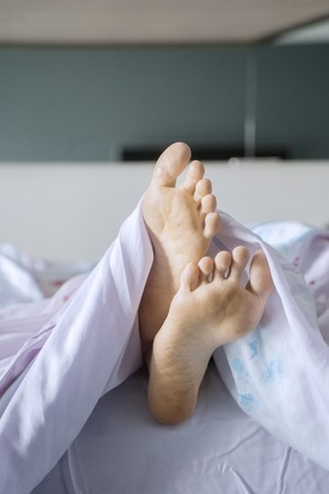Feet of unknown woman sticking out from under a blanket during sleeping on the bed Stock Photo