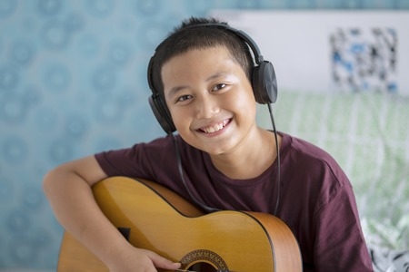 Portrait of a cute little boy wearing headset while playing acoustic guitar. Shot at home