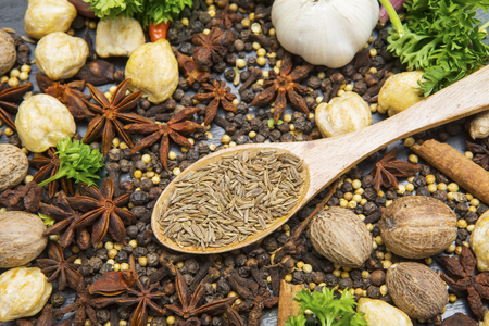 Top view of caraway seeds in a wooden spoon with variety spices above kitchen table
