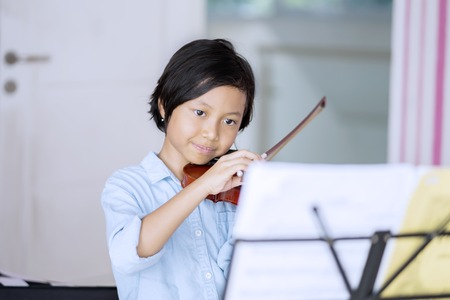 Picture of a little girl looking at paper notes while practicing and playing violin at home Stock Photo
