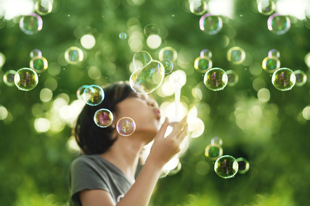 Image of a little girl standing in the park while blowing soap bubbles with blur background