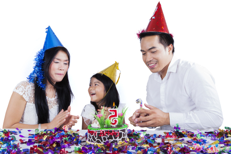 Young family clapping hands together while celebrating a birthday, isolated on white background