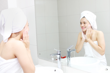 Portrait of Asian woman wearing towel after bathing while washing her face with a soap