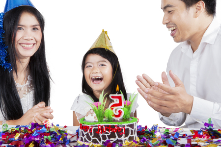 Happy family clapping hands together while celebrating a birthday, isolated on white background