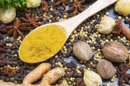 Close up of fresh turmeric powder on the wooden table with various spices above the table Stock Photo