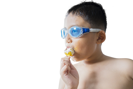 Summer concept. Cute little boy wearing a swim glasses while eating an ice cream, isolated on white background