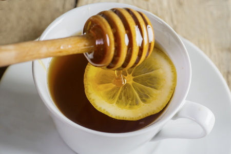 Closeup of healthy tea with slice of lemon and honey. Shot above wooden table Stock Photo
